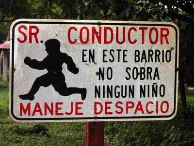 Cartel: Señor conductor: en este barrio no sobra ningún niño. Conduzca despacio.