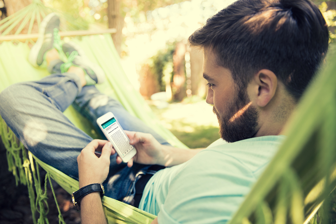 Man lying on hammok and using smartphone outdoors